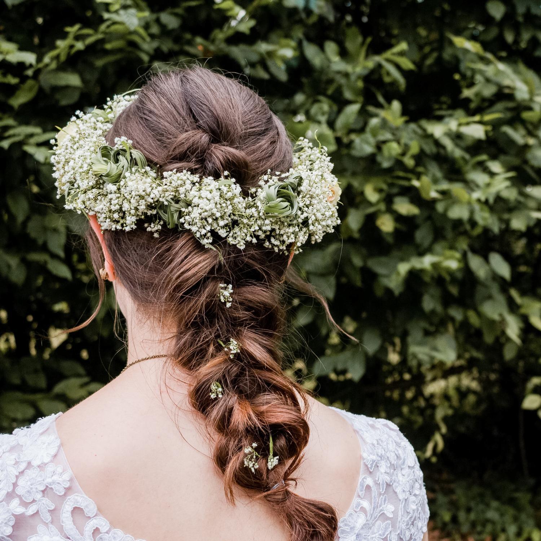 Brautfrisur für lange Haare, mit geflochtenem Zopf und Vintage-Blumenkranz