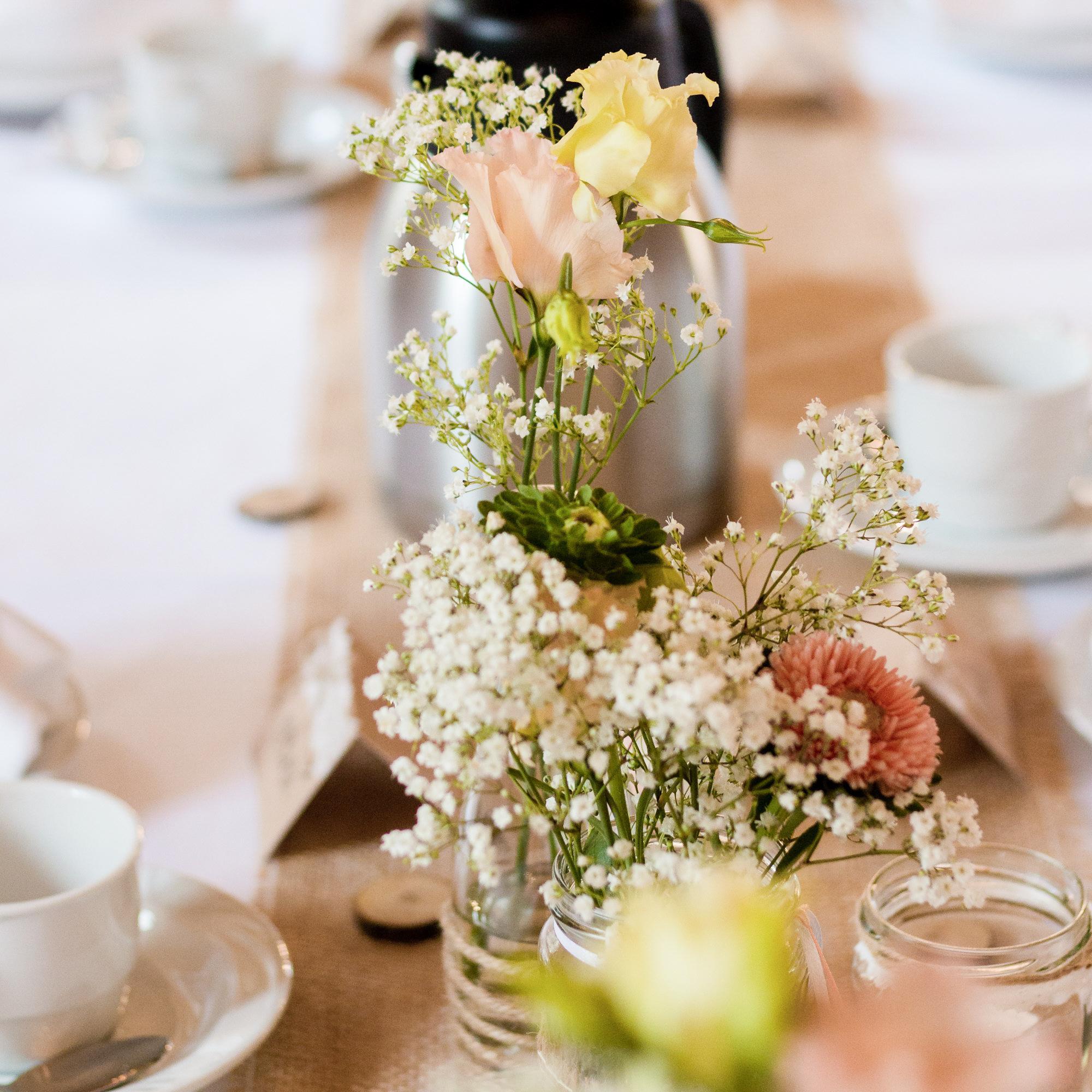 Tischdekoration für eine Sommerhochzeit im Landhaus-/Vintage-Stil, wilde Blumendeko mit Schleierkraut und apricotfarbenen sowie pastellgelben Blüten