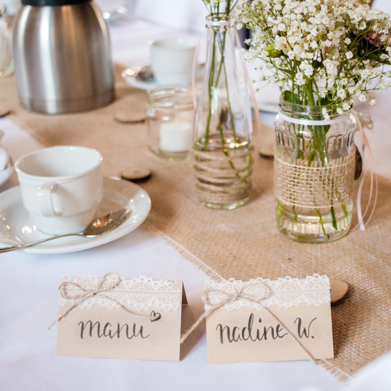 Tischdekoration für eine Sommerhochzeit im Landhaus-/Vintage-Stil, Tischkarten aus Kraftpapier, im Lettering-Stil beschrieben