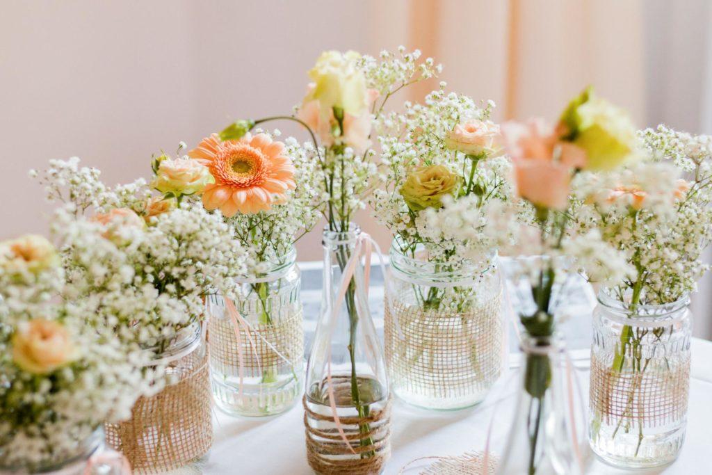 Hochzeitsdekoration für eine Sommerhochzeit im Landhaus-/Vintage-Stil, wilde Blumendeko aus Schleierkraut, Gerbera, Rosen und Astern